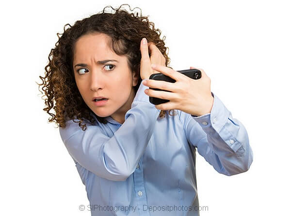 Lady worried about hair loss looking in the mirror